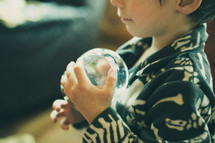 a boy child holding a snow globe