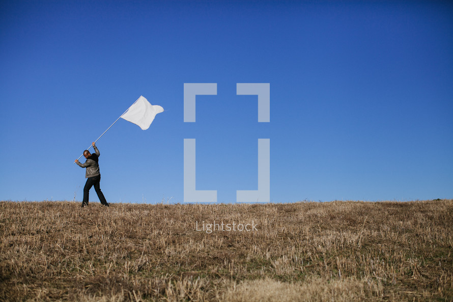 business man in a field holding a white flag - surrendering