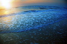 tide washing onto a shore at sunset