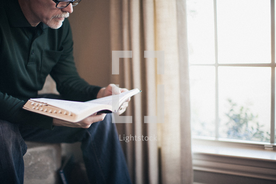 elderly man sitting in front of a window reading a Bible by sunlight