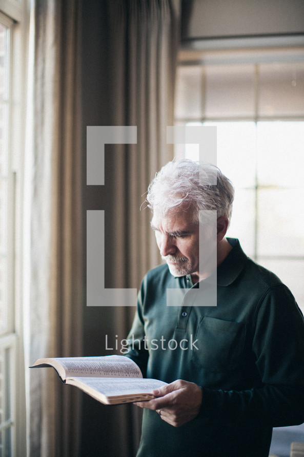 Man reading Bible in front of window.