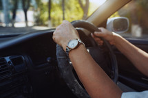 man's hands on a steering wheel