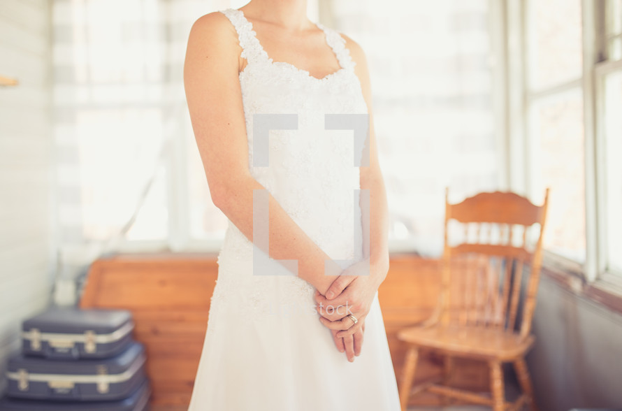 torso of a bride standing in a wedding dress