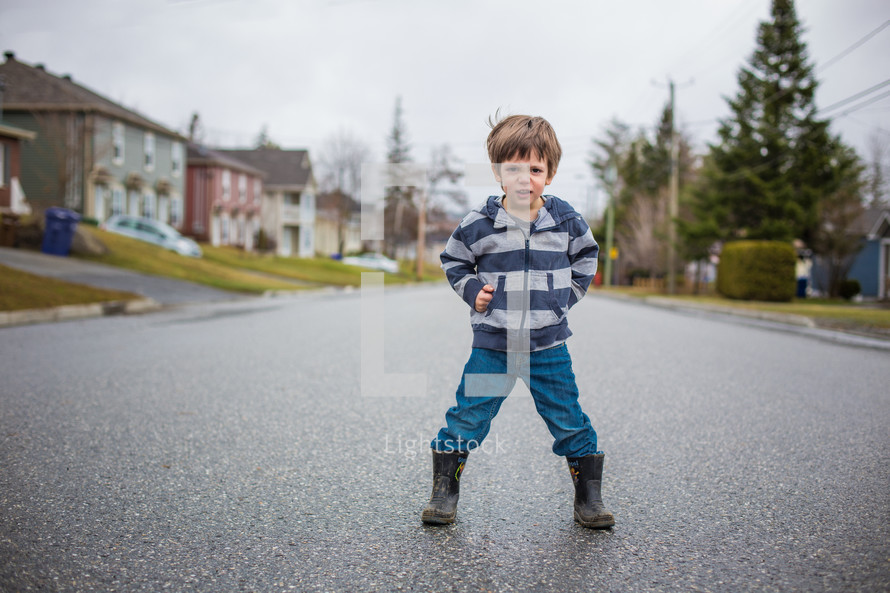 a boy child standing in the middle of a neighborhood street