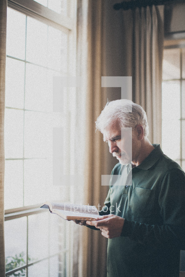 elderly man standing in front of a window Reading a Bible by sunlight