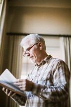 elderly man standing at a window reading a Bible