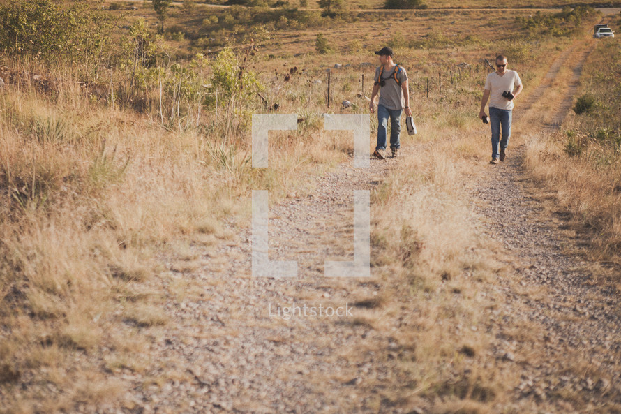 Two men walking up a hill on a dirt road.