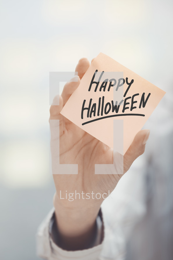 woman holding a sticky note with the words Happy Halloween