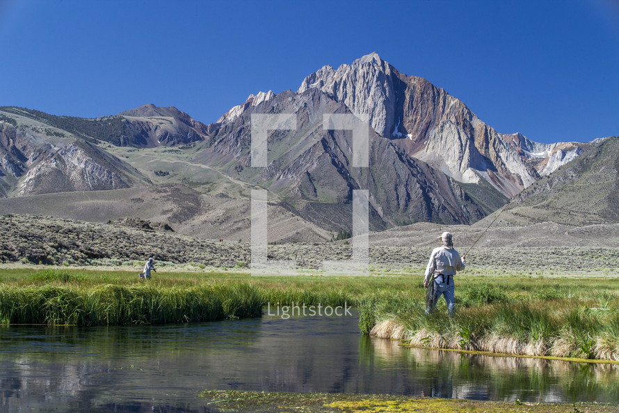 fly fishing in a river near a mountain