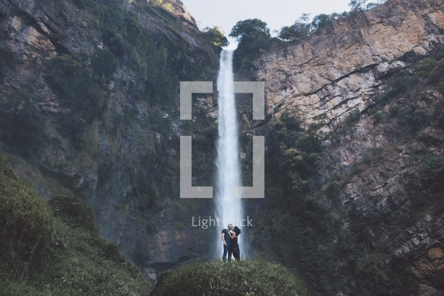 a couple kissing in front of a waterfall