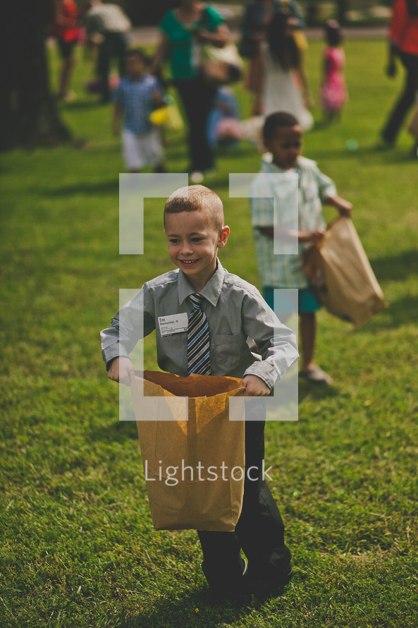 children with paper bags during an Easter egg hunt