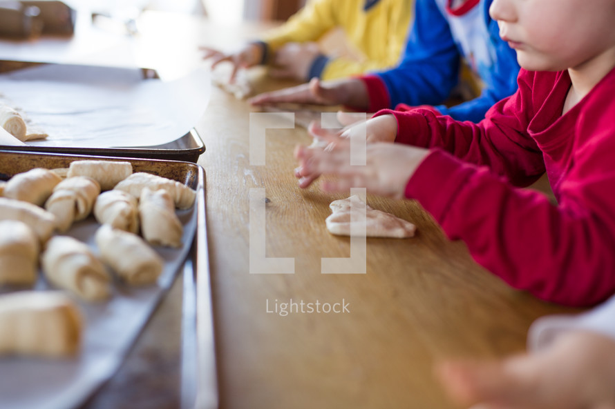 boys rolling crescent rolls
