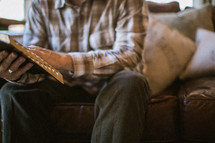 torso of an elderly man sitting on a couch reading a Bible