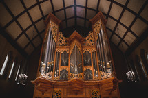 An ornate pipe organ in a church.