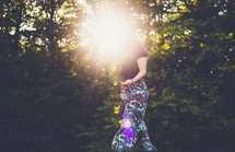 sunburst and a woman walking outdoors