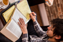 man reading a book and taking notes