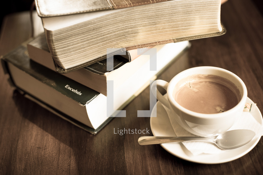 stack of books and a coffee cup with spoon