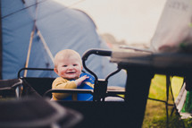 an infant in a wagon in front of a tent