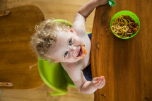 A little boy in a high chair eating spaghetti.