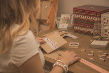 A woman sitting at a crafting desk working with stamps.