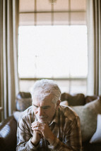 elderly man sitting on a couch praying