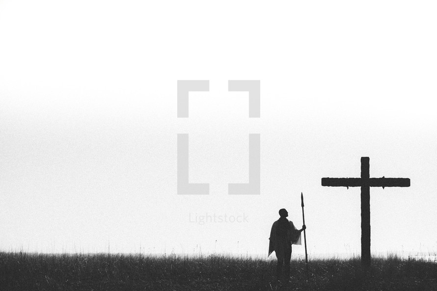 Roman soldier with spear standing in front of the cross.