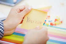 a woman reaching for a sticky note with the words you can