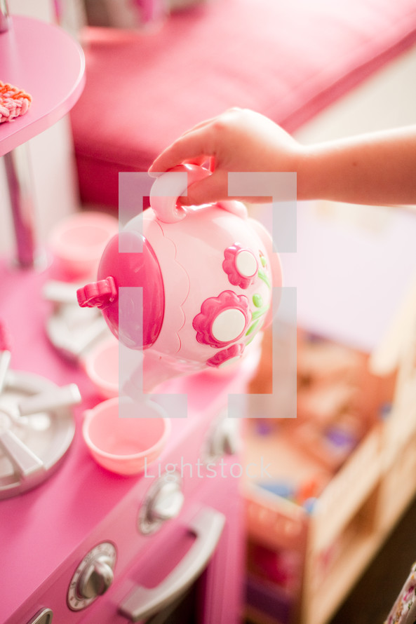 toddler girl playing with a toy kitchen