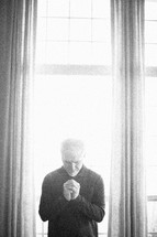 elderly man standing in front of a window praying by sunlight
