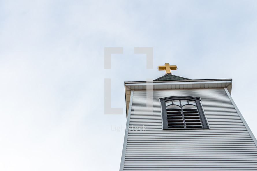 Looking up at church steeple with golden cross
