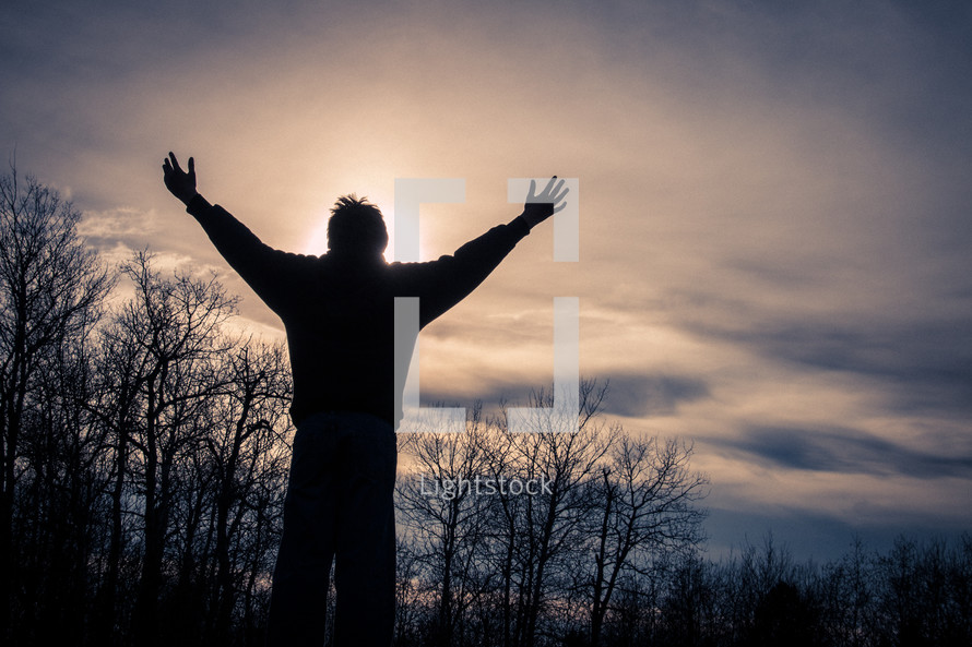 Man with arms outstretched in praise during sunset