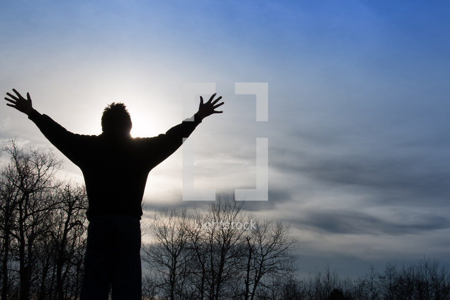 Man praising God in sunset with outstretched arms up