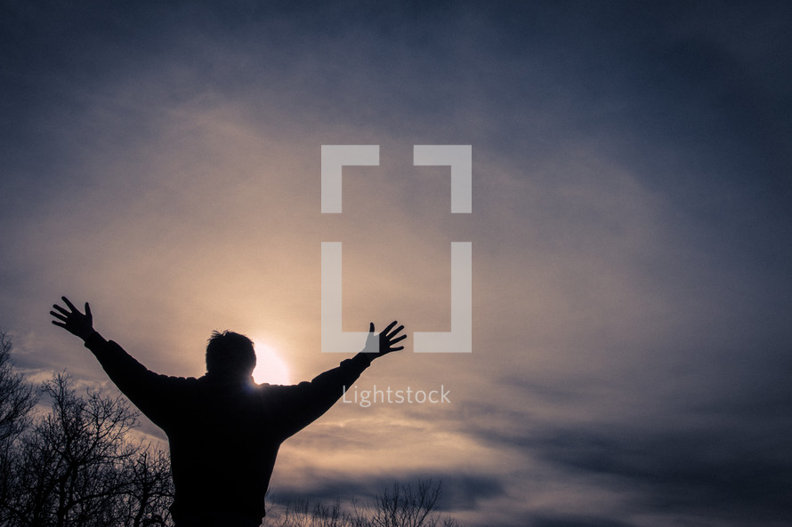 Backlit man with arms up in sunset