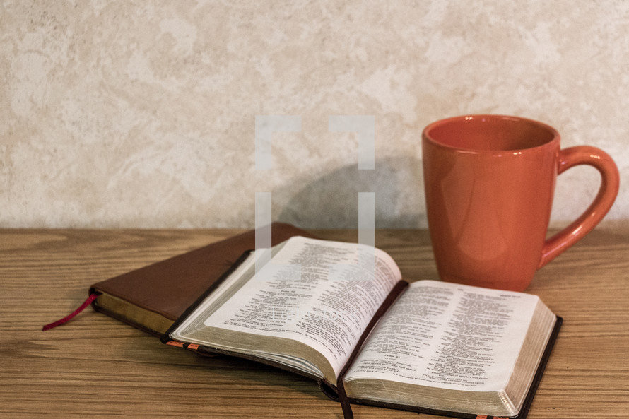 Bible open on desk with coffee cup and brown leather journal