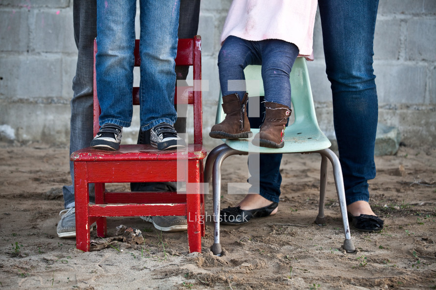 The legs of a man and woman standing behind a boy and girl who are standing in chairs placed in the dirt