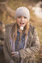 girl child eating marshmallows off a stick