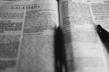 pen lying on a Bible open to Galatians