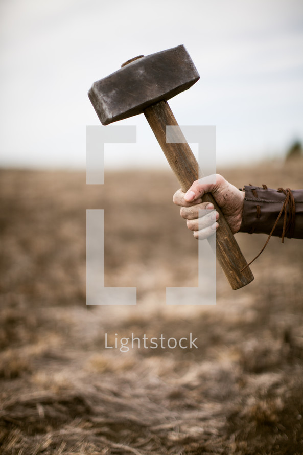 Roman soldier holding hammer above the cross.