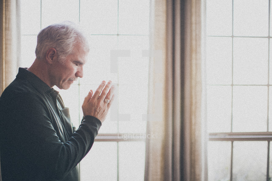 elderly man standing at a window in prayer