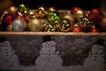 Multi-colored Christmas balls in a wooden box painted with snowmen.
