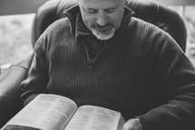 A man reading a Bible sitting in a chair