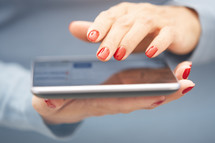 a woman touching a tablet screen