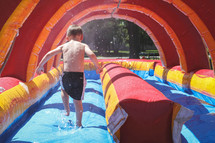 boy on a bounce house water slide