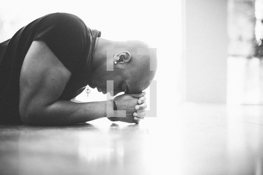 Man with head on hands praying on the floor.