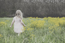 toddler girl in a field of tall grasses and wildflowers
