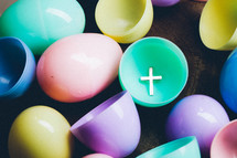Silver cross inside colorful plastic Easter egg.
