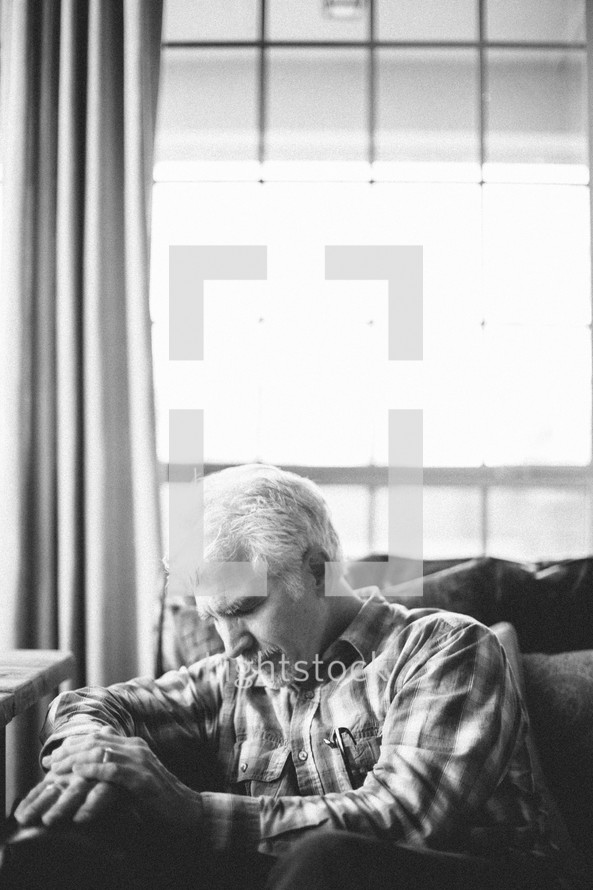 elderly man sitting on a couch with his head bowed in prayer