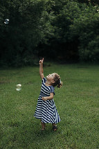 a toddler girl chasing bubbles in the grass