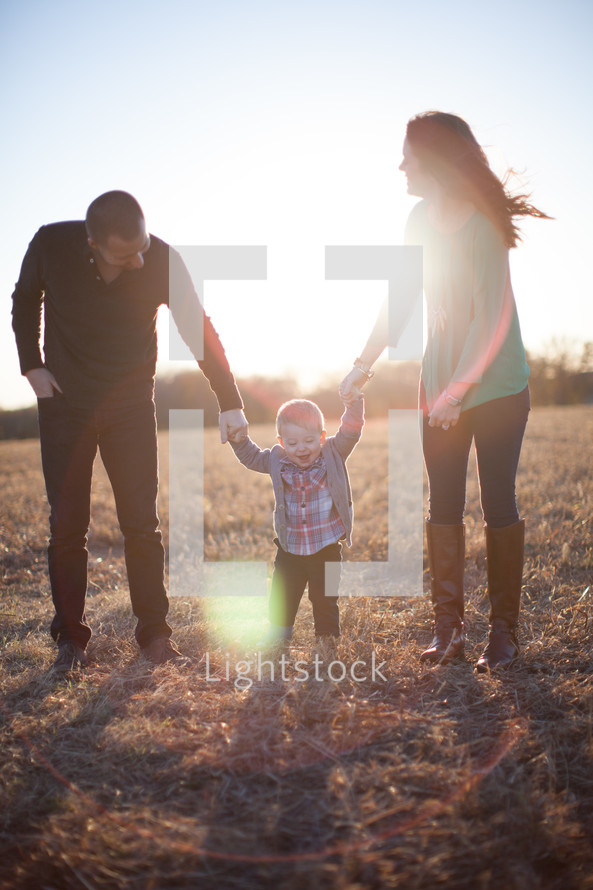 A white mom and dad help their child walk in a field.