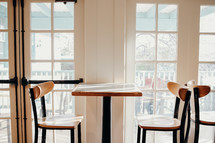 empty dinette table and chairs in front of a window
